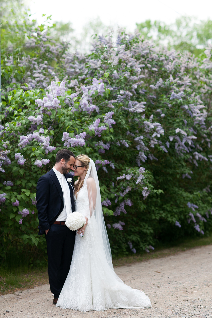 Bridal couple smiling at each other in front of a lilac bush.