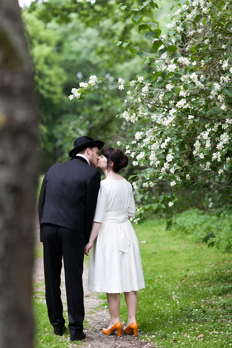 Bridal couple kissing on front of a tree.