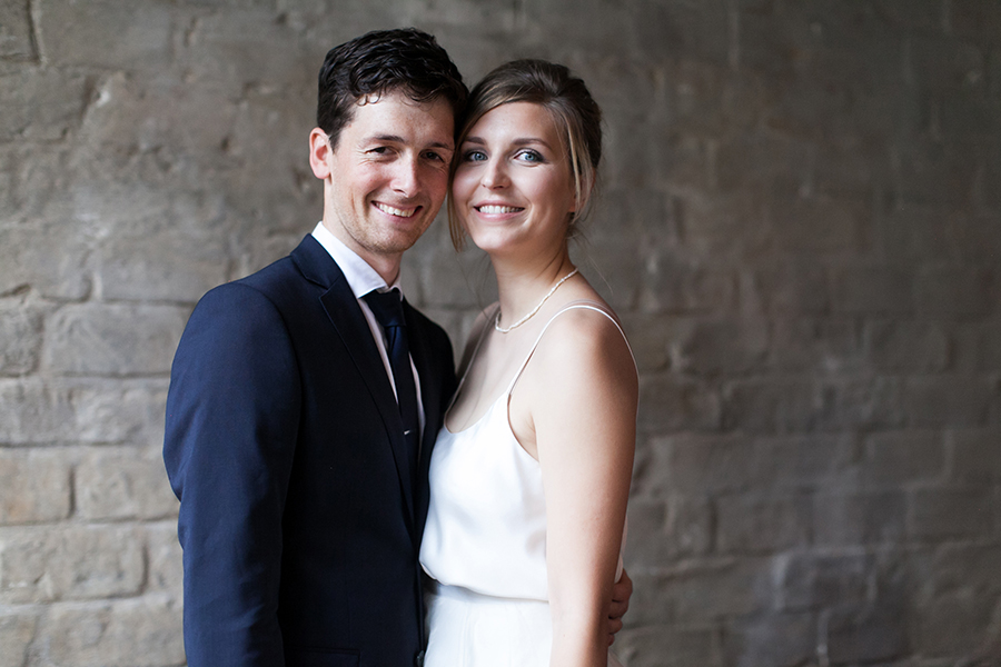 Bridal couple smiling into the camera.